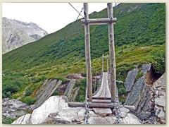 34_Die neue Hängebrücke unter der kristallklares Wasser duch ein felsiges Bachbett flirsst. Bei Pt 1924 trennen sich zwei Täler