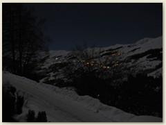03_Abend-Licher im Dorf Vella und beleuchtete Pistenfahrzeuge