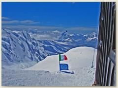 25 Vor dem Hütteneingang erinnern uns die Fahnen wo wir sind. Die Berghütte beherbergt wissenschaftliche Einrichtungen für höhenmedizinische Experimente und ein Observatorium