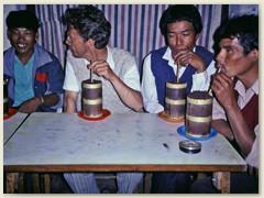 """76 Das Nationalgetränk """"Tongba"""" Gegorene Hirse im Holzbecher, heisses Wasser, mit einem Bambusrohr trinken"""